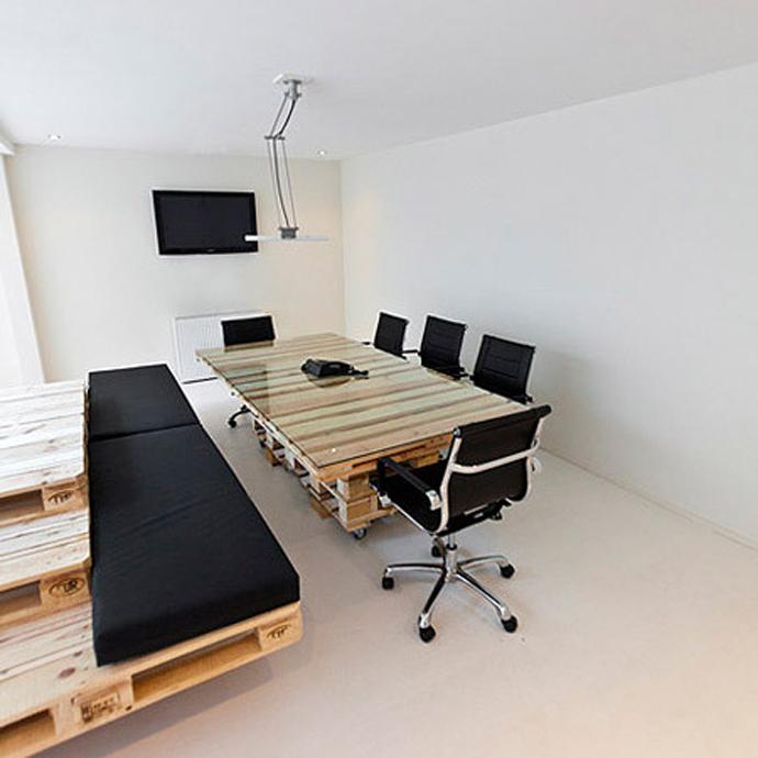 משרד של חברת מולטימדיה - שולחן עשוי מכמה משטחי עץ עם משטח זכוכית וספה בצד המשרד.
