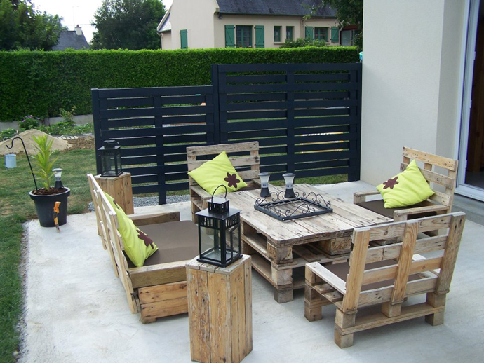 שולחן עשוי משלושה משטחי עץ וספסלים שעשויים מחלקים של משטחי עץ.